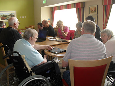 A group of older people learning about tablet computers