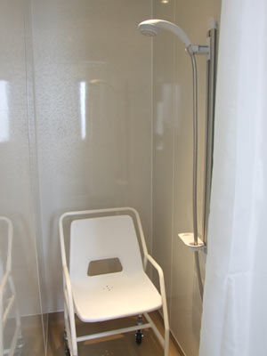 Adapted shower with roll in roll out chair